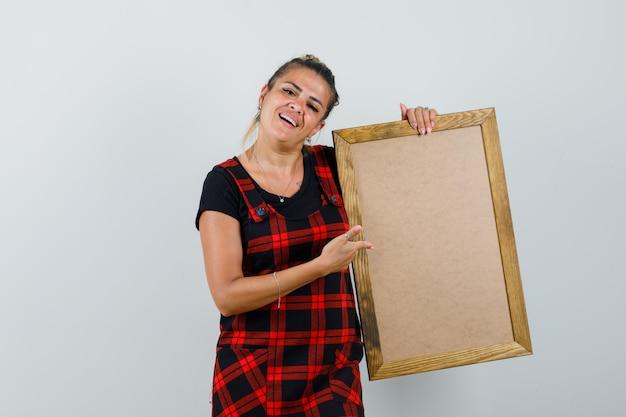 Kobieta pokazuje pustą ramkę w stroju fartuszka i patrząc zadowolony, widok z przodu.