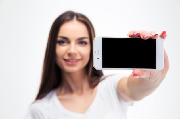 Kobieta pokazuje pusty ekran smartfona