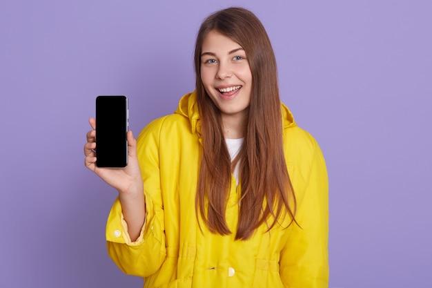 Kobieta pokazuje pusty wyświetlacz inteligentny telefon z radosnym uśmiechem, pozowanie na białym tle nad liliową ścianą, ubrany w żółtą koszulkę.