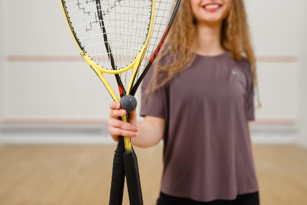 Kobieta pokazuje rakietę do squasha i piłkę. dziewczyna na treningu gry, aktywne hobby sportowe na korcie