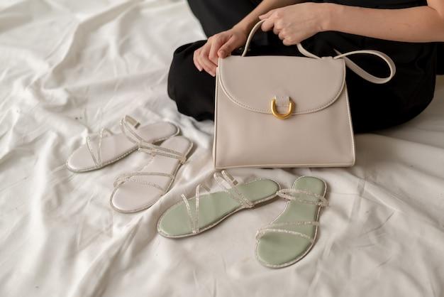 Kobieta pokazuje rzemienną mody torbę, sandały i