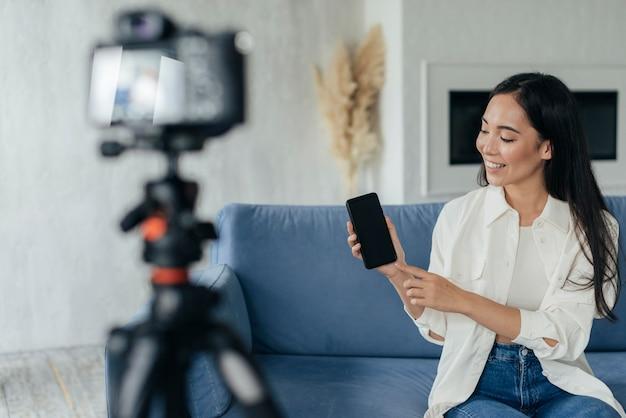 Kobieta pokazuje swój telefon podczas vlogowania