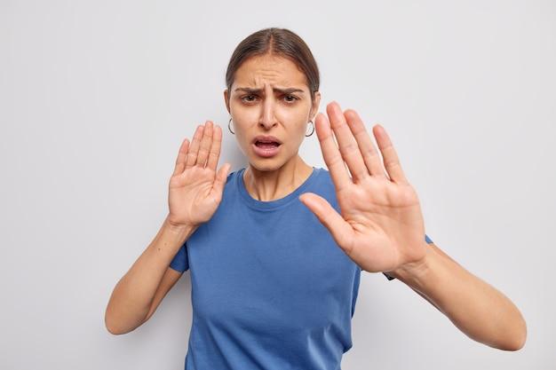 Kobieta pokazuje swoje zaprzeczenie opinia mówi trzymaj się z daleka uspokój się lub powoli prosi o zachowanie dystansu demonstruje gest tabu ubrana swobodnie na białej ścianie
