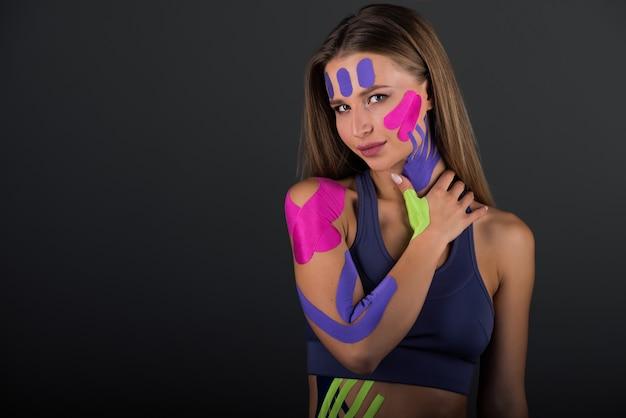 Kobieta pokazuje taśmy kinezjologiczne przyklejone do brzucha. jasna taśma medyczna na brzuchu i nodze