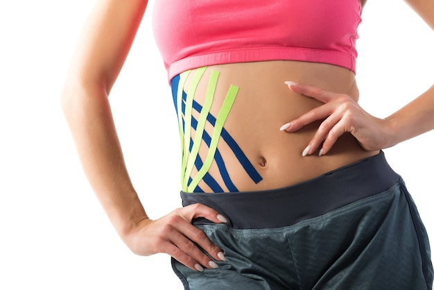 Kobieta pokazuje taśmy kinezjologiczne przyklejone do brzucha