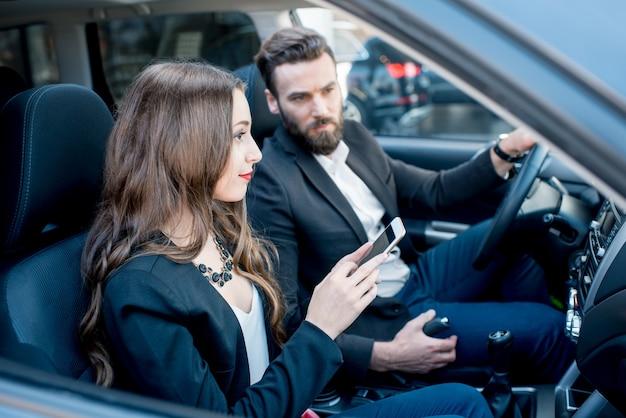 Kobieta pokazuje telefon biznesmenowi siedzącemu razem z przodu w samochodzie
