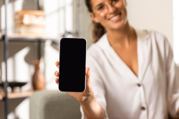 Kobieta pokazuje telefon deski