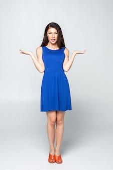 Kobieta pokazuje z dwa otwartymi rękami. piękna urocza kobieta w lato sukni odizolowywającej w pełnym ciele.