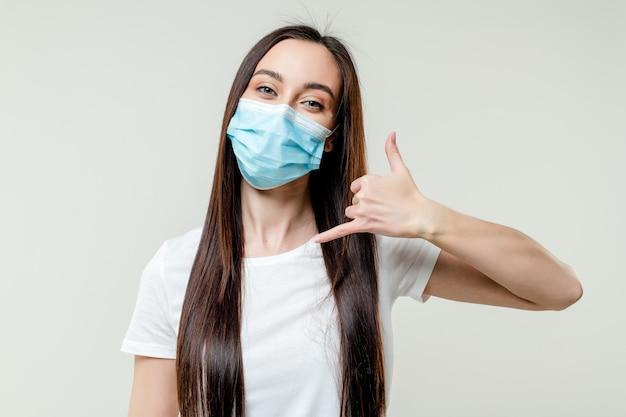 Kobieta pokazuje zadzwoń do mnie noszenie maski