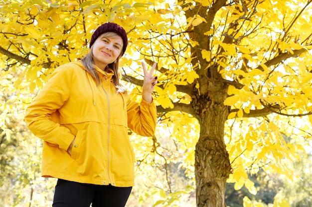 Kobieta pokazuje znak pokoju na tle żółtych jesiennych liści. pozytywny