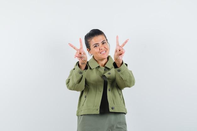 Kobieta pokazuje znak v w kurtce, koszulce i wygląda wesoło.