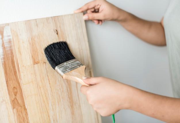 Kobieta pokrywa drewnianą deskę z lakierem