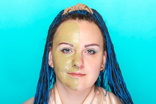 Kobieta pół twarzy w masce z zielonej glinki na niebieskiej ścianie.