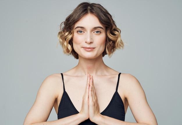 Kobieta połączyła dłonie razem na szarym tle i medytacji fitness sportowej