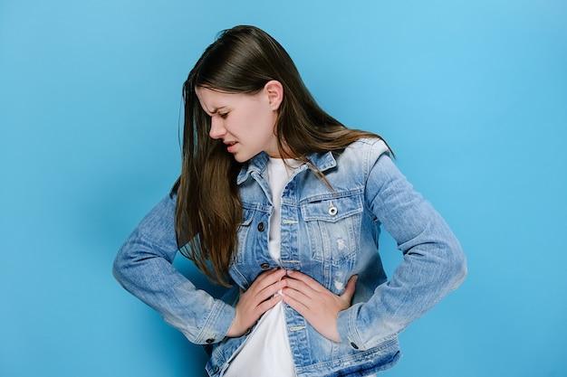 Kobieta położyła ręce na brzuchu cierpiąc na ból brzucha, smagając się