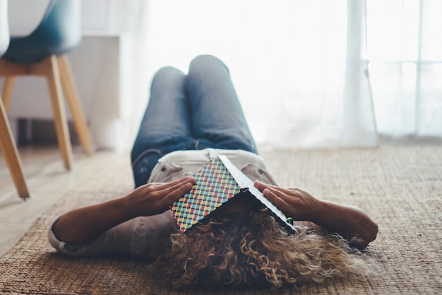 Kobieta położyła się na podłodze na dywanie śpiąc, bo zmęczona książką do zasłaniania oczu. kobiety śpiące w ciągu dnia w salonie. pojęcie zdrowia choroby bezsenności