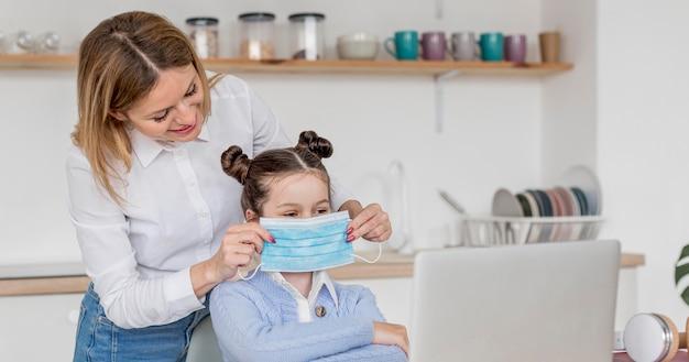 Kobieta pomaga córce położyć maskę medyczną