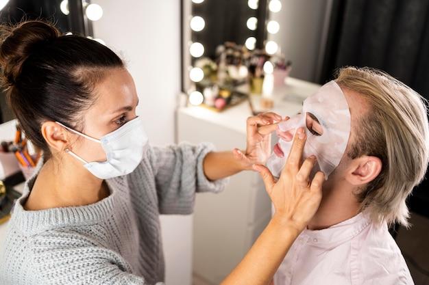 Kobieta pomaga człowiekowi stosując maseczkę na twarz