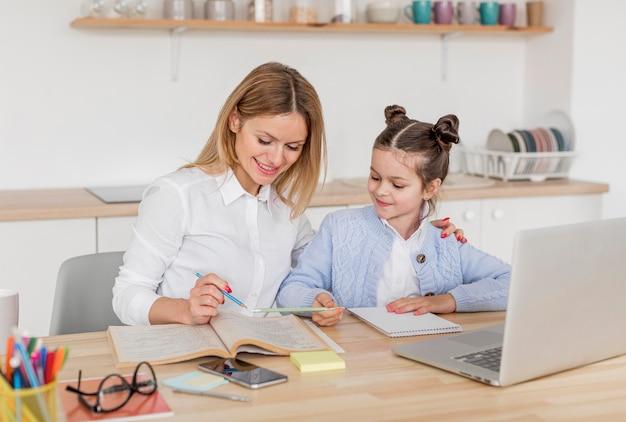 Kobieta pomaga jej córki z pracą domową w domu