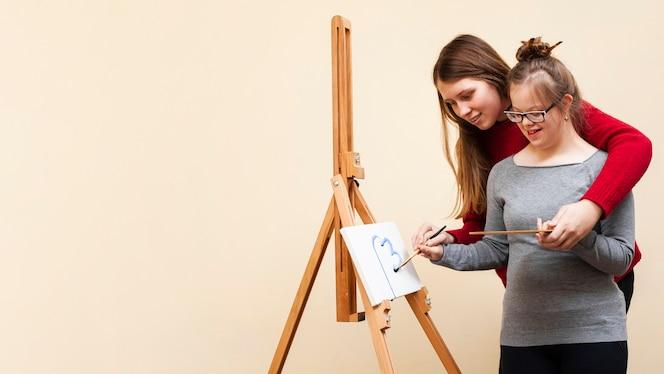 Kobieta pomaga smiley girl z zespołem Downa farby