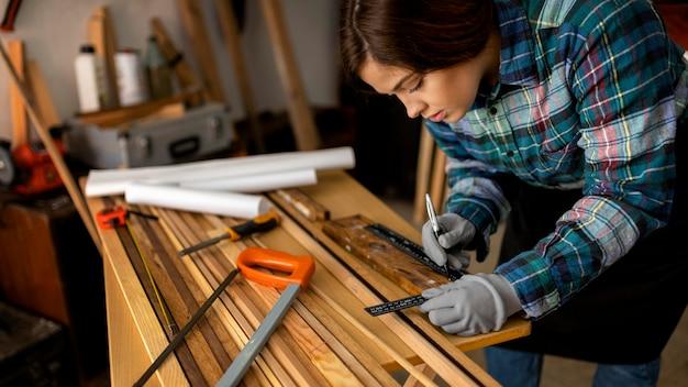 Kobieta pomiaru desek drewnianych