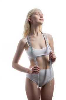 Kobieta pomiaru kształtu pięknej talii z uśmiechem na pojęcie zdrowego stylu życia na białym tle.