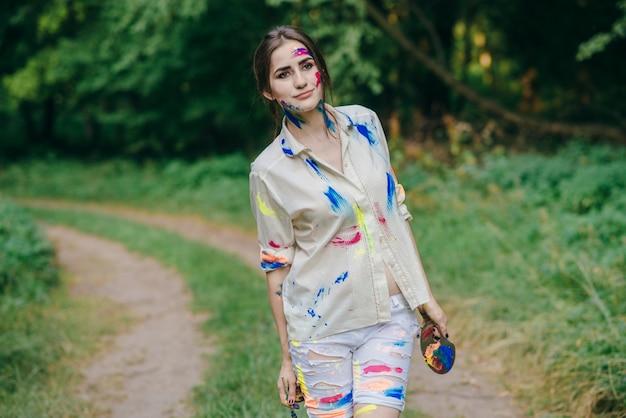 Kobieta poplamione farbą chodzenie na polnej drodze
