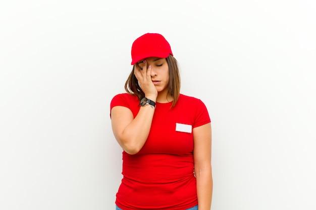 Kobieta poręczona znudzona, sfrustrowana i śpiąca po męczącym, nudnym i żmudnym zadaniu, trzymając twarz ręką na białym
