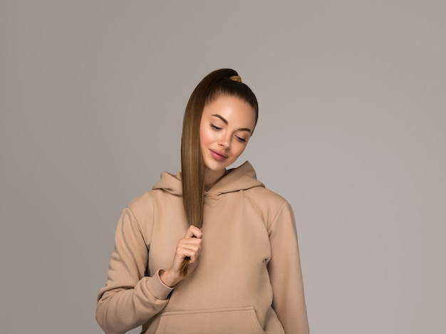Kobieta portret dorywczo studio naturalne kobiece długie włosy. kolor tła. szary