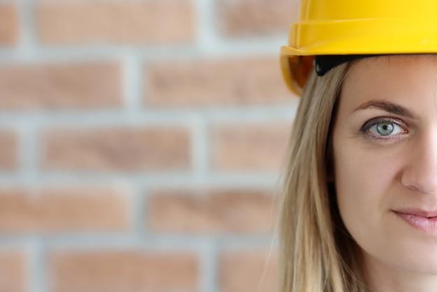 Kobieta portret konstruktora w żółtym kask na tle ściany