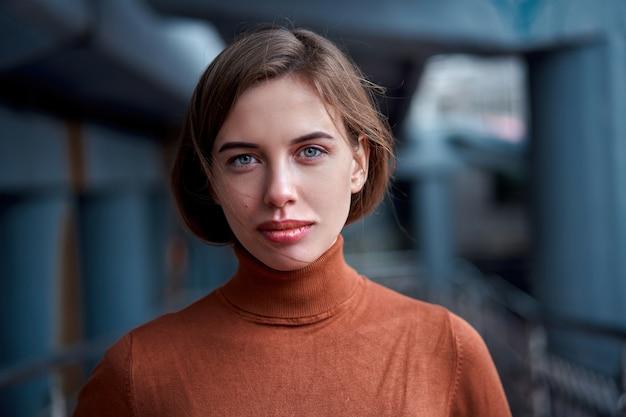 Kobieta portret pewności siebie brunetka ubrana w brązowy golf z dramatyczną atmosferą
