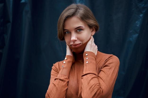 Kobieta portret pewności siebie brunetka ubrana w brązowy golf