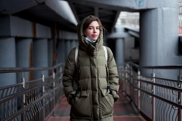 Kobieta portret pewności siebie brunetka ubrana w ciepłą kurtkę zimową z dramatyczną atmosferą