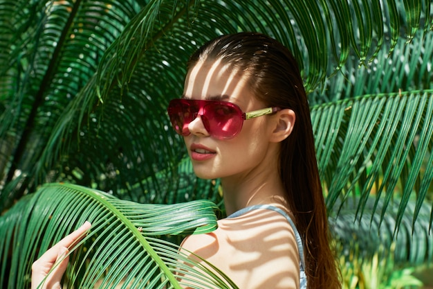 Kobieta portret w szkłach na zieleni liście drzewka palmowe, piękna twarz