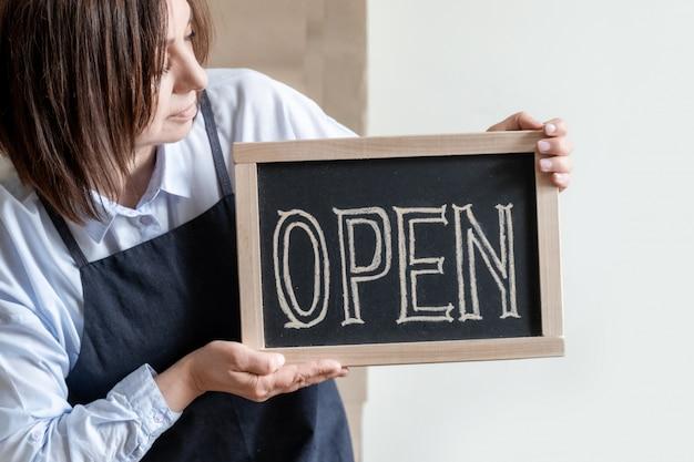 Kobieta posiada zarządu z tekstem otwarte. pracownik w fartuchu pokazuje otwarcie kawiarni lub rynku.