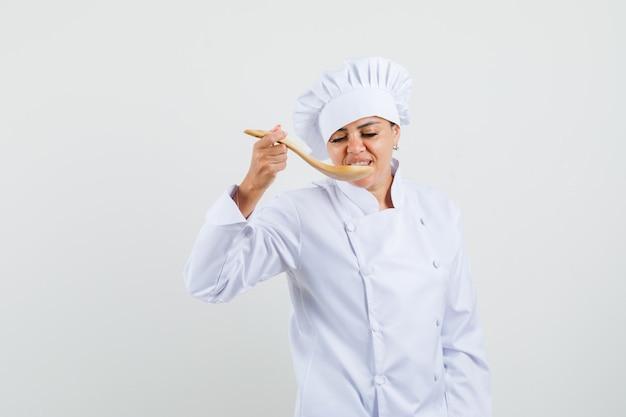 Kobieta posiłek degustacyjny szefa kuchni z drewnianą łyżką w białym mundurze