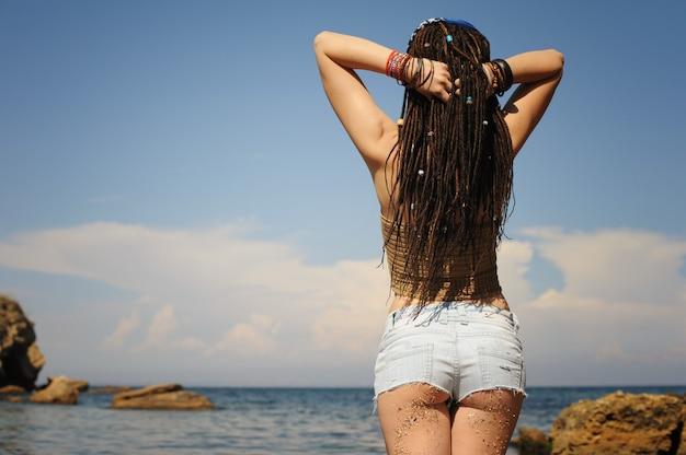 Kobieta pośladek brudny piaskiem na tle słonecznego krajobrazu, dżinsowe szorty