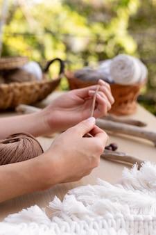 Kobieta posługująca się techniką makramy
