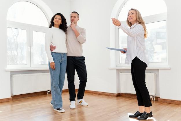 Kobieta pośrednik w handlu nieruchomościami pokazano młodej pary nowy dom