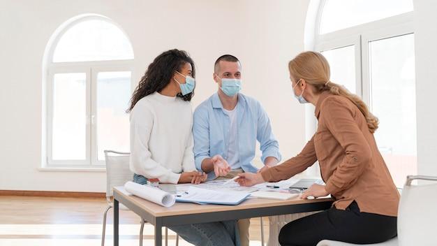 Kobieta pośrednik w handlu nieruchomościami pokazuje parę z planami domu maski medyczne