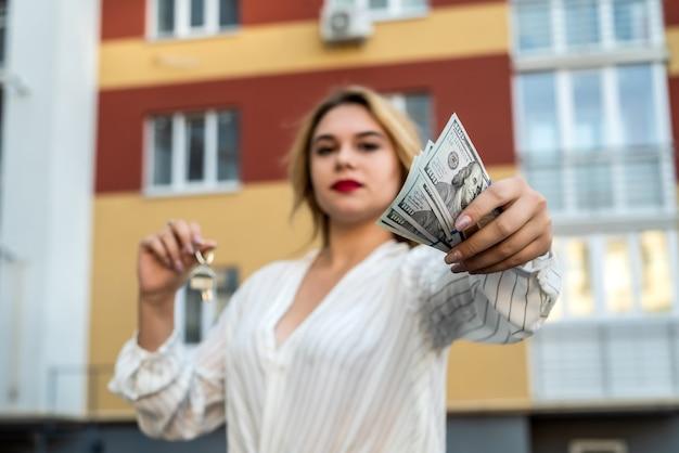 Kobieta pośrednik w handlu nieruchomościami trzymając brelok w kształcie małego domu i klucze przed domem jako tło