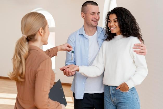 Kobieta pośrednik w handlu nieruchomościami wręcza buźkę para klucze do ich nowego domu