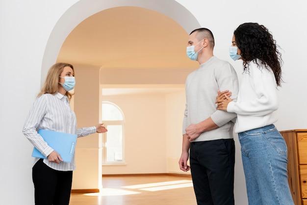 Kobieta pośrednik w handlu nieruchomościami z maską medyczną przedstawiający kilka nowych domów