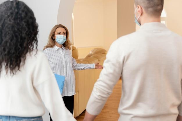 Kobieta pośrednik w handlu nieruchomościami z maską medyczną zaprasza parę do obejrzenia nowego domu