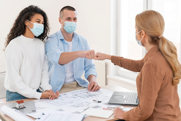 Kobieta pośrednik w handlu nieruchomościami z pięścią w masce medycznej wpadając na parę nad stołem z planami domu