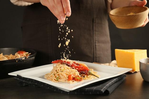 Kobieta posypująca serem spaghetti z kurczaka