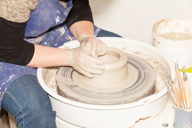 Kobieta potter tworząca gliniany słoik na kole pottera