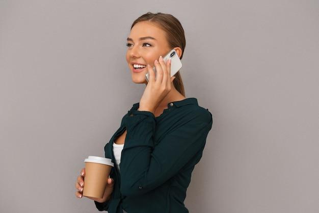 Kobieta pozowanie na białym tle nad szarym tle ściany picia kawy rozmawia przez telefon komórkowy.