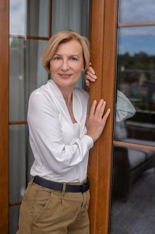 Kobieta pozuje do kamery przy otwartych drzwiach zewnętrznych