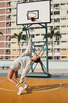 Kobieta pozuje na boisko do koszykówki w hongkongu